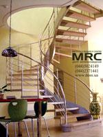 Спиральная лестница на тетиве. Ограждения лестницы из полированной нержавеющей стали, ступени из твердых пород дерева