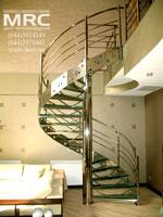 Винтовая металлическая лестница с центральной опорной стойкой и тетивой. Каркас и ограждения лестницы из  полированной нержавеющей стали, ступени из каленого стекла
