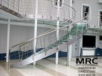 Металлическая  криволинейная лестница на тетивах. Каркас и ограждения лестницы из полированной нержавеющей стали,  ступени из безопасного архитектурного стекла