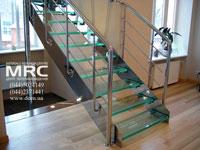 Металлическая  прямая лестница на тетивах. Каркас и ограждения лестницы из полированной нержавеющей стали,  ступени из безопасного архитектурного стекла