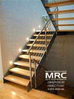 Двухмаршевая лестница на тетивах. Ограждения лестницы из полированной нержавеющей стали, ступени из твердых пород дерева
