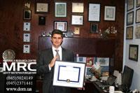 Профессор Юрий Гогоци в своем рабочем кабинете с дипломом Distinguished Professor Award