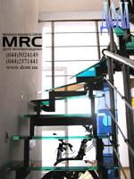 Лестница в квартире с разноцветными ступенями из стекла триплекс