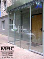Glass entrance lobby. Handling of glass door from polished stainless steel